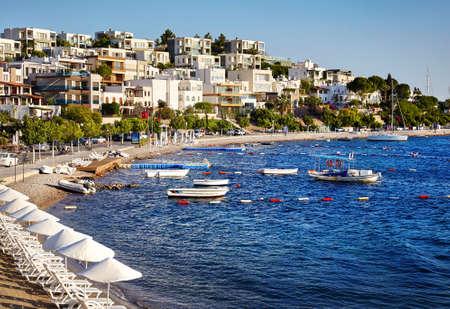 Hoteles y Paraguas blancos cerca de la laguna con barcos en la playa en Bodrum, Turquía Foto de archivo - 78779250