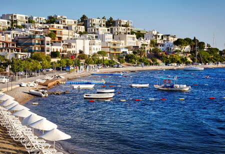Hotels and White Umbrellas near lagoon with boats on the beach in Bodrum, Turkey