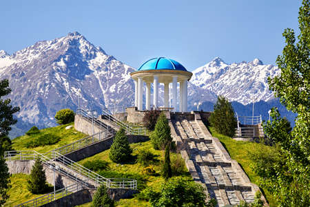 View to the monument with at snowy mountains background in dendra park of first president Nursultan Nazarbayev in Almaty, Kazakhstan