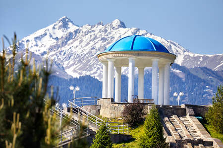 Monument with column at snowy mountains background in the park of first n Almaty, Kazakhstan