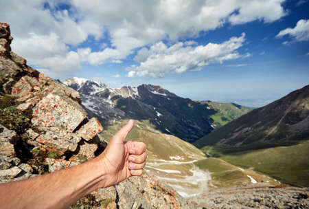 survive: Traveler Man showing thumb up in the snowy mountains Stock Photo