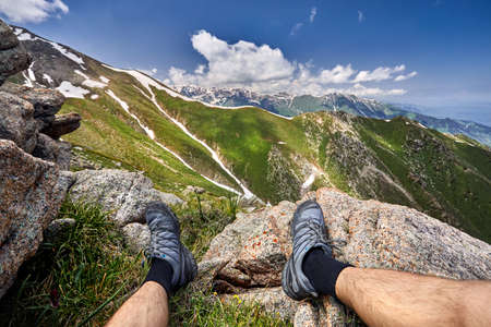 Legs of man in tracking shoes and view of Snowy Mountains with cloudy sky background