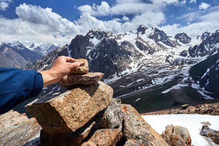 Traveler putting stone on the pyramid in the snowy mountains