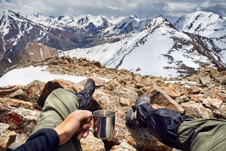 Man holding cup with hot tea with view of Snowy Mountains with cloudy sky background