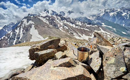 Touristic Mug with tea on the stones with snowy mountains view Stock Photo