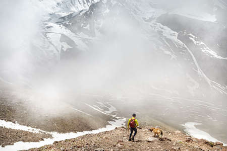 Hiker in green shirt with backpack and dog walking in the snowy mountains at foggy sky background