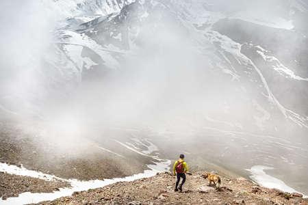 Wanderer im grünen Hemd mit Rucksack und Hund zu Fuß in die schneebedeckten Berge bei nebligen Himmel Hintergrund Standard-Bild - 80820510