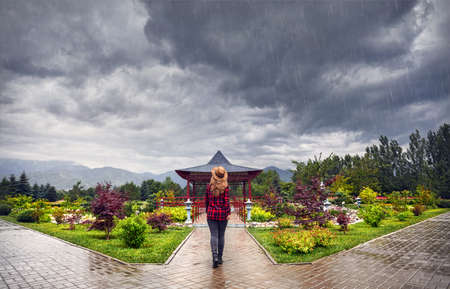 Woman in red checked shirt and hat going to the Japanese Pagoda garden at rainy overcast sky Sajtókép