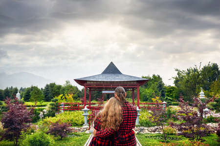 Young Couple in red checked shirts hugging and looking to the Japanese Pagoda garden at overcast sky