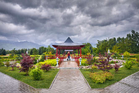 Young Couple in red checked shirts hugging each other near Japanese Pagoda garden at rainy overcast sky Editorial