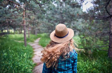 森の松の木の下で風に長い髪の流れと茶色の帽子と緑のチェックのシャツの若い女性