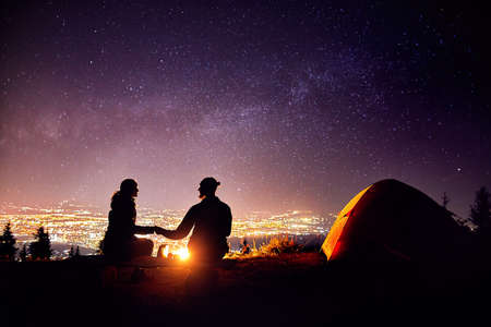 Happy couple in silhouette sitting near campfire and orange tent. Night sky with milky way stars and city lights at background.
