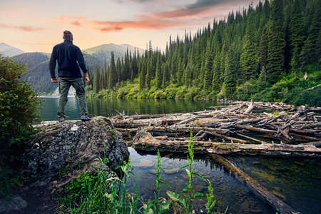 Hiker in black shirt standing on the stone and looking on mountain lake with forest at sunrise sky background