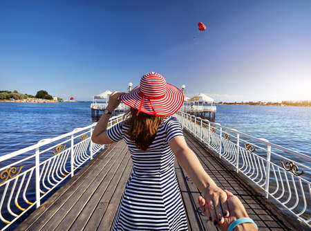 Woman in red Hat and striped dress holding his boyfriend by hand and walking to the pier in Ruh Ordo cultural complex at Issyk Kul lake with mountains background in Cholpon Ata, Kyrgyzstan