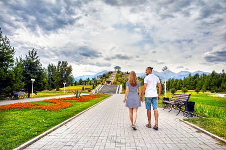 Happy couple in holding by hands and walking down the famous park in Almaty, Kazakhstan Stock Photo