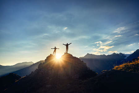 Two Hikers in silhouette stands on the rock in the beautiful mountains with rising hands at sunrise sky background Archivio Fotografico
