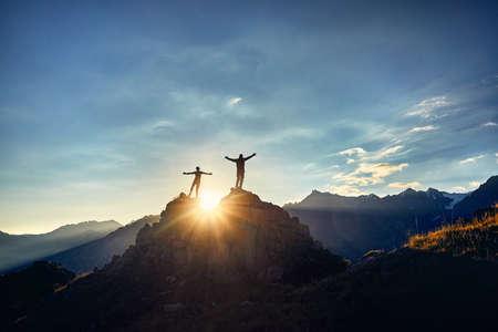 Twee wandelaars in silhouet staan op de rots in de prachtige bergen met rijzende handen bij zonsopgang hemelachtergrond