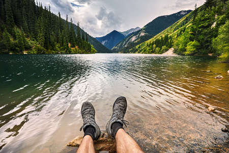 Travelers leg with shoes at beautiful view of high mountain lake Kolsai at summertime in Kazakhstan, central Asia