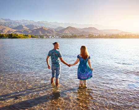 Beautiful couple standing in crystal clean water of Issyk Kul lake with mountains background at sunrise in Kyrgyzstan photo