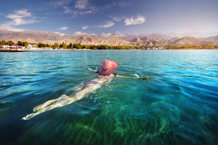 Beautiful woman in red striped hat swimming in crystal clean Issyk Kul lake with mountains background at sunrise in Kyrgyzstan