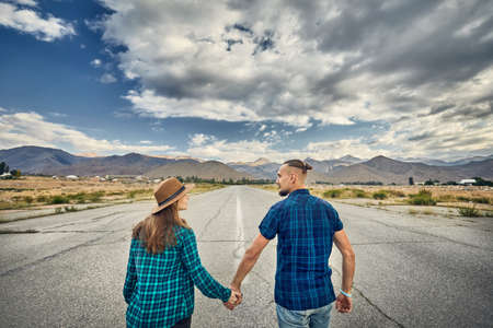 Happy couple in checked shirt holding by hands and walking on the wide asphalt road with mountains and cloudy sky background