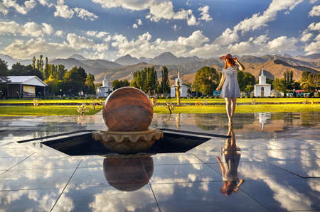 Tourist woman in red Hat and striped dress walking down the hall with stone sphere in Ruh Ordo cultural complex at Issyk Kul lake with mountains background Kyrgyzstan Editöryel