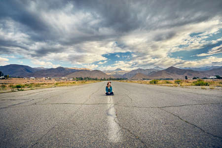 Woman in hat and checked shirt sitting with cross leg on the wide asphalt road with mountains and cloudy sky background Фото со стока
