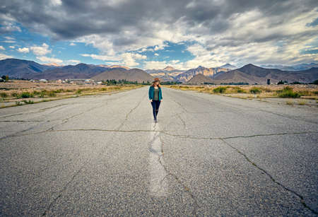 Woman in hat and checked shirt walking on the wide asphalt road with mountains and cloudy sky background