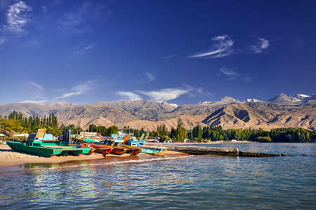 Colorful Old school boats and catamarans on the beach of Issyk Kul Lake in Kyrgyzstan
