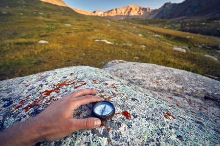 Tourist hand with vintage compass on the mountains background. Travel and adventure concept.