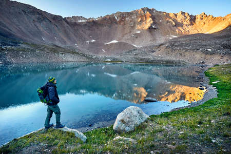 Bearded man in green hat and backpack looking at mountain lake at sunrise