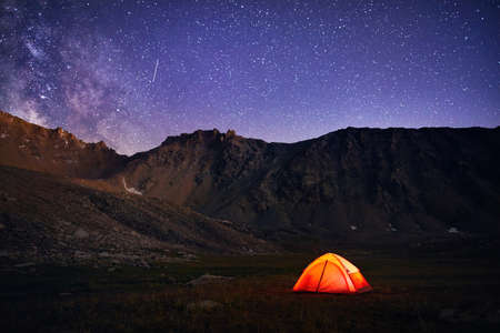 Orange tent glows under night sky full of stars and Milky way in the mountains in Kazakhstan