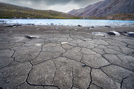 Cracked soil and Mountain Lake at grey overcast sky background