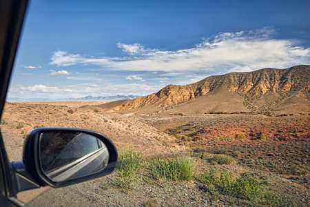 scenic drive: Wild Landscape desert canyons from the window of the car on the road in Kazakhstan