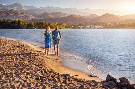 Beautiful couple walking on the beach water of Issyk Kul lake with mountains background at sunrise in Kyrgyzstan