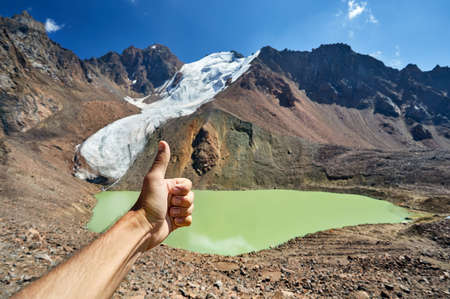 Hand of tourist with thumb up at Mountain Lake background Stock Photo