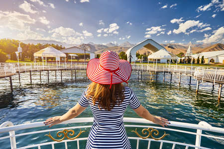 Tourist woman in red Hat and striped dress on the pier in Ruh Ordo cultural complex Issyk Kul lake with mountains background at sunset in Cholpon Ata, Kyrgyzstan Stok Fotoğraf