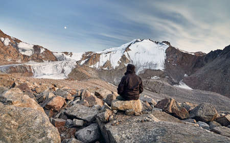 Hiker in brown jacket on stones in front of high snowy mountains at rising moon background