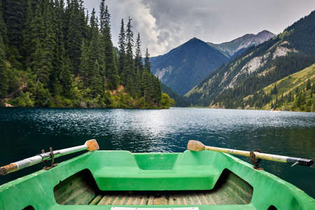 Beautiful view of mountain lake Kolsai and green boat at foreground in Kazakhstan Stock fotó