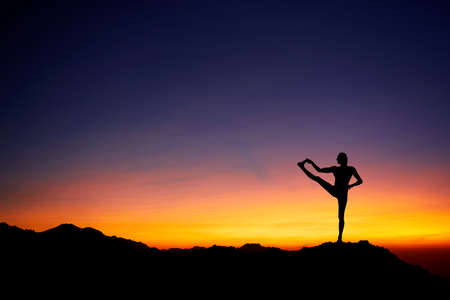 Fit Man in silhouette doing yoga balance pose at beautiful orange sunset sky background Stock Photo
