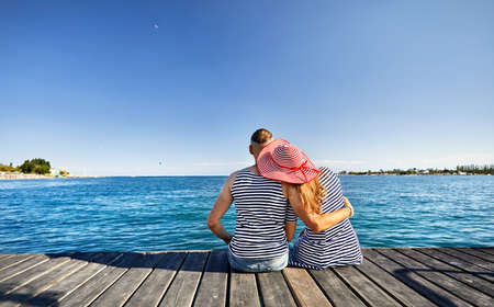 Romantic couple in striped dress sitting on pier and looking at blue lake Issyk Kul in Kyrgyzstan Stok Fotoğraf