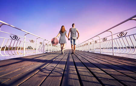 Woman in striped dress with red hat and man in stripped shirt going on the pier near lake at the pink sunset Stok Fotoğraf