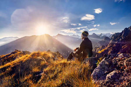 Tourist in Nepali hat sitting on the hill and looking at sunrise in the mountains