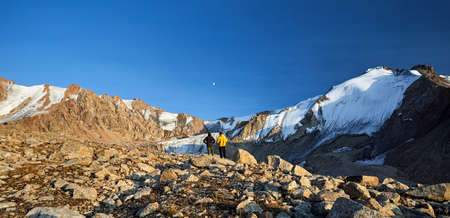 Hikers in yellow and dark jackets on stones in front of high snowy mountains at rising moon background