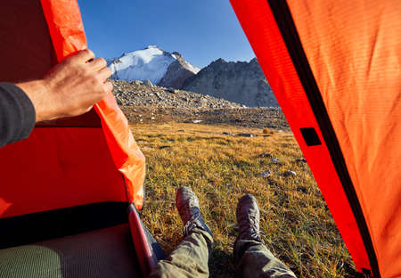Hiker legs from orange tent with view to beautiful snowy summit