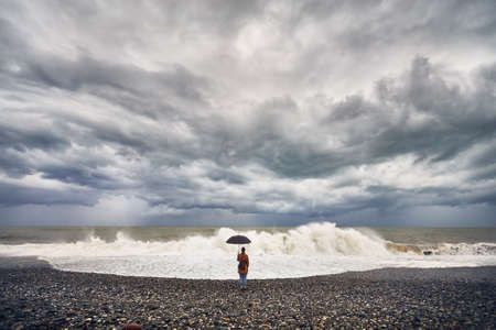 Woman with umbrella and backpack looking at stormy sea and overcast sky in Batumi, Georgia Stock Photo