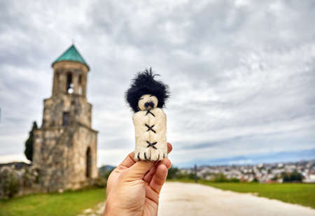 Georgian traditional puppet of man in hat papaha near Bagrati Cathedral at overcast sky in Kutaisi, Georgia