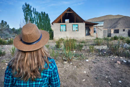 Woman in hat and checked shirt looking at ruined old house in the village Stock Photo