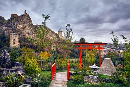 Japanese garden and old castle Narikala at overcast cloudy sky in botanical garden of Tbilisi, Georgia Editorial