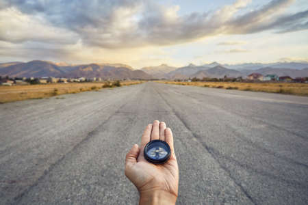 Traveler holding compass on the road with mountains at sunrise sky background. Travel and adventure concept.